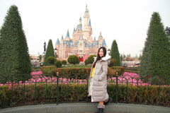 A Chinese woman stand in front of Disney Castle in Shanghai of China. A Chinese girl stand in front of Shanghai Disney Castle in Shanghai of China, in winter stock photos