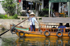 Chinese woman standing and rowing boat Royalty Free Stock Images