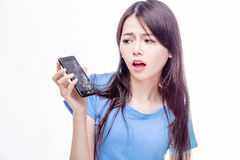 Chinese woman staring at broken cell phone. Asian woman looking at broken smartphone in disbelief stock photography