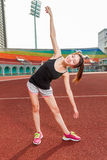 Asian American woman stretching on track at stadium Stock Image