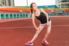 Chinese woman stretching on track at stadium Royalty Free Stock Photography