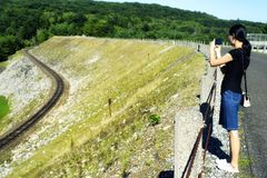 A Chinese woman taking pictures of a railroad track along an earthen dam royalty free stock image