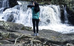 Chinese woman taking pictures of waterfall. A chinese woman taking pictures of the waterfall at Southford Falls State Park in Spring in Oxford Connecticut royalty free stock image