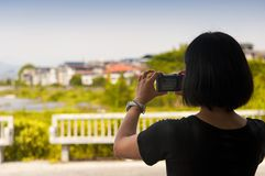 Chinese woman taking pictures in Wuyishan. A chinese woman taking pictures of the Wuyishan or Mount Wuyi scenic area in Fujian province China stock image