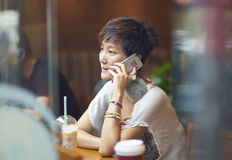 A chinese woman talking on smartphone in coffee shop Stock Image