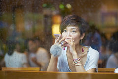 A Chinese woman talking to smartphone in coffee shop Royalty Free Stock Photo