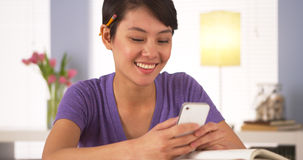 Chinese woman texting classmate on smartphone Royalty Free Stock Photo