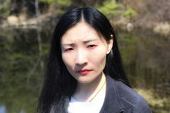 Chinese woman at topsmead state forest connecticut. A chinese woman looking serious at the camera at Topsmead state forest in Litchfield Connecticut on a spring royalty free stock images