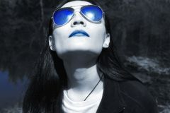 Chinese woman looking to the future. A chinese woman looking up at the sun outside in nature in black and white with blue lipstick and sunglasses royalty free stock photography