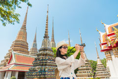 Chinese woman tourist photographer taking pictures. With dslr of the wat pho temple Bangkok, Thailand. asian girl visiting and looking around the sightseeing Royalty Free Stock Image
