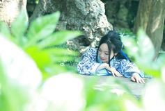 Chinese woman in traditional Blue and white Hanfu dress Climb over the stone table Stock Photo