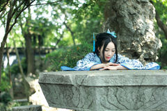 Chinese woman in traditional Blue and white Hanfu dress Climb over the stone table. Chinese woman in traditional Hanfu dress Climb over the stone table at Qiyuan Royalty Free Stock Images
