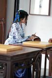 Chinese woman in traditional Blue and white Hanfu dress play the game of go Royalty Free Stock Photo
