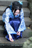Chinese woman in traditional Blue and white Hanfu dress Sit on the steps and paddle. Chinese woman in traditional Hanfu dress Sit on the steps and paddle at Royalty Free Stock Image