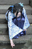 Chinese woman in traditional Blue and white Hanfu dress Sit on the steps and paddle. Chinese woman in traditional Hanfu dress Sit on the steps and paddle at Royalty Free Stock Photos
