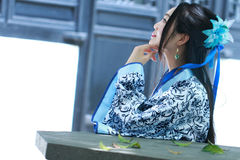 Chinese woman in traditional Blue and white Hanfu dress Sit on the stone bench Stock Photo