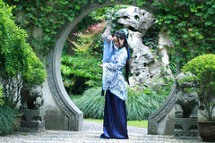 Chinese woman in traditional Blue and white Hanfu dress Standing in the middle of beautiful gate Stock Photos