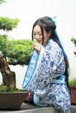 Chinese woman in traditional Blue and white Hanfu dress Standing next to bonsai Stock Photo