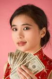 Chinese woman with US money 20 dollar bill. Portrait of young beautiful Chinese female in traditional clothes (cheongsam) holding pile of US paper currency royalty free stock photography