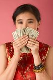 Chinese woman with US money 20 dollar bill. Portrait of young beautiful Chinese female in traditional clothes (cheongsam) holding US paper currency twenty stock photography