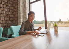 Chinese  Woman using cell telephone while relaxing after work on portable net-book. Beautiful lady chatting on smart phone while sitting at the table with laptop Royalty Free Stock Image