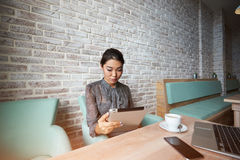 Chinese  Woman using cell telephone while relaxing after work on portable net-book. Beautiful lady chatting on smart phone while sitting at the table with laptop Stock Photo