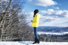 Chinese woman using a selfie stick. A Chinese woman wearing a yellow winter jacket takie a selfie on a cold winter day in West Stockbridge Massachusetts stock photos