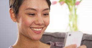 Chinese woman using smartphone on couch Stock Photo