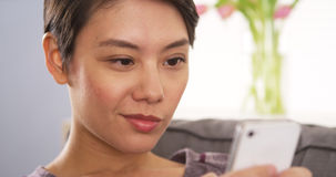 Chinese woman using smartphone on couch Royalty Free Stock Images