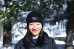 A chinese woman wearing a mountain hardwear winter hat. A smiling chinese woman wearing a mountain hardwear brand winter hat outside in Torrington connecticut on royalty free stock photo