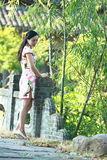 A Chinese woman wears Cheongsam in the water park of Shanghai royalty free stock photo