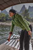 Chinese woman working ferryman on the river Lijiang, Guangxi, Ch Royalty Free Stock Photography