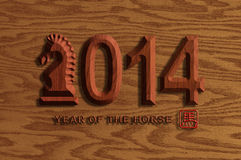 2014 Chinese Wood Chiseled Horse on Wood Grain Background. 2014 Chinese Lunar New Year of the Horse Wood Chiseled Numerals with Horse Text Symbol Wood Grain Royalty Free Stock Photo