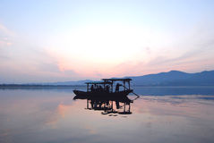 Chinese wooden boat drifting on a lake in sunset Royalty Free Stock Photos