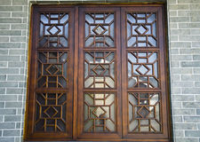 Chinese wooden windows on the brick wall. Chinese wooden windows with patterns Stock Image