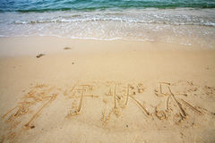 Chinese word 'happy new year' write on beach Royalty Free Stock Photo
