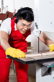 Chinese worker on saw in industrial factory Royalty Free Stock Photos