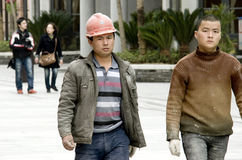 Chinese workers. Two Chinese peasant workers walk in a street ,wearing dirty clothes,they came from poor area far from city.Photo taken in Wuhan city of China Royalty Free Stock Photo
