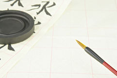 Chinese writing brush on bottom right and ink stone. Red Chinese writing brush on bottom right and ink stone on yellow practice paper royalty free stock photo