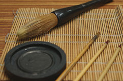 Chinese writing brush and ink stone on brush mat. Chinese writing brush and ink stone on Keep brush mat stock photo