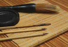 Chinese writing brush and ink stone. On Keep brush mat royalty free stock image