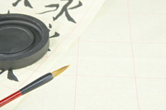 Chinese writing brush and ink stone on practice paper Royalty Free Stock Photos