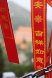 Chinese writing on a red tape on Lantau Island, Hong Kong. Chain in the foreground with blurred monastery in the background stock photos