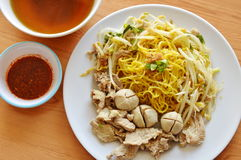 Chinese yellow noodle topping boiled pork and soup with cayenne pepper sauce Royalty Free Stock Image