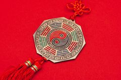 Chinese yin and yang talisman on red surface. Close-up shot of chinese yin and yang talisman on red surface stock photo