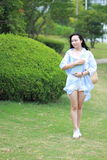 Chinese Young attractive student girl with long hair posing in  campus green park carrying book Stock Images