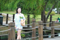 Chinese Young attractive student girl with long hair posing in  campus green park carrying book Royalty Free Stock Image