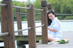 Chinese young beautiful woman sit on bridge see lake in park. Close to nature,Enjoy leisure time stock images