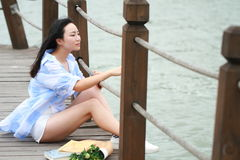 Chinese young beautiful woman sit on bridge see lake in park. Close to nature,Enjoy leisure time royalty free stock image