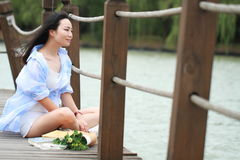 Chinese young beautiful woman sit on bridge see lake in park. Close to nature,Enjoy leisure time royalty free stock photography